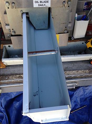 seamless aluminum gutter coming out of a gutter machine